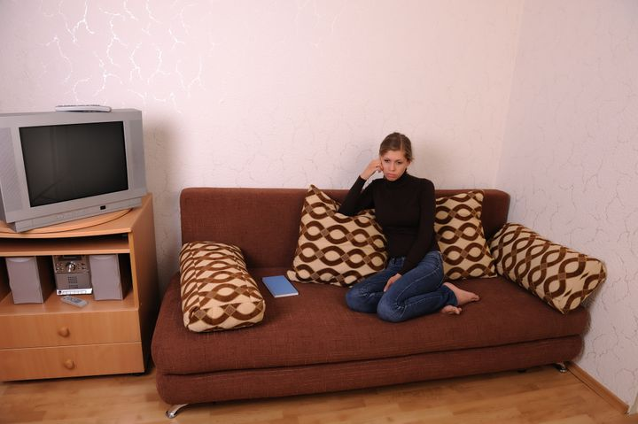 A young and sad woman in a living room