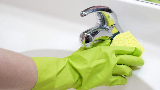 A person cleaning the bathroom sink with a glove