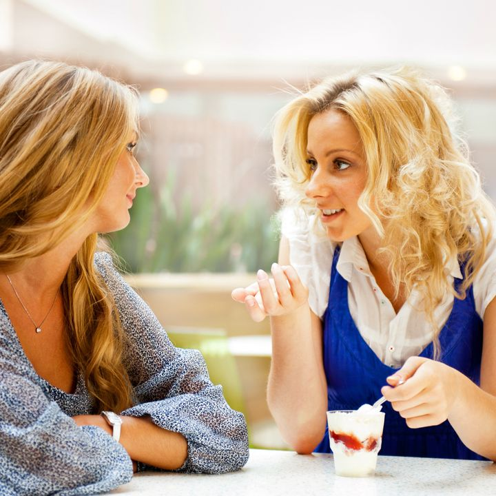 Two beautiful women drinking coffee and chatting at mall cafe.