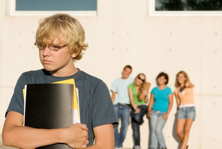 students boy being bullied by other group of students