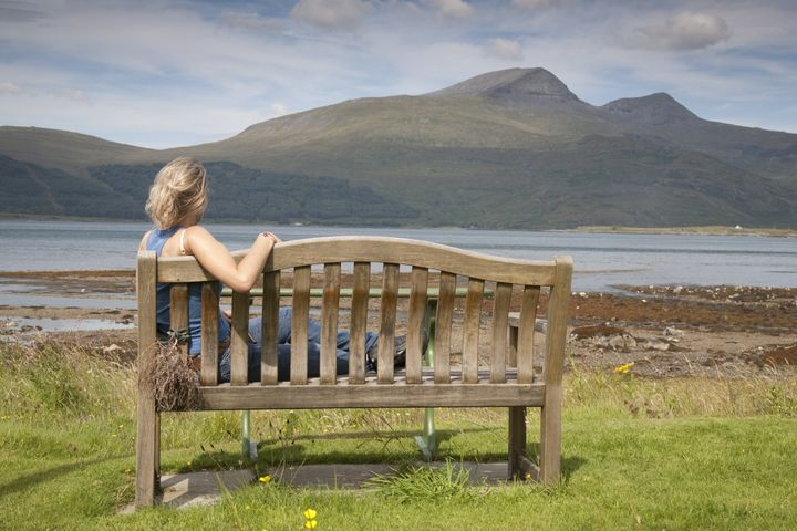 young woman sitting on bench on ...