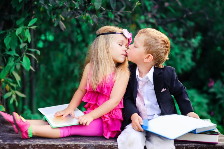 Adorable happy kids outdoors on summer day, little boy kissing a girl