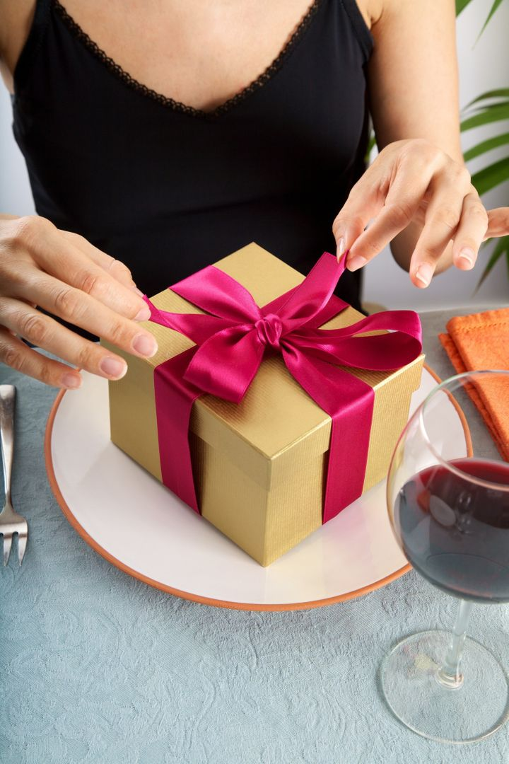 woman at restaurant opening a golden gift package