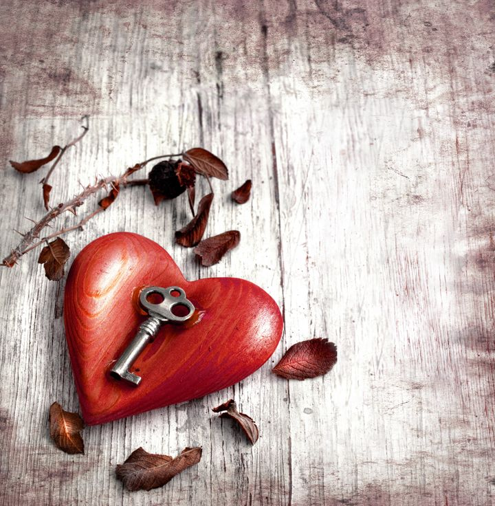 Key with the heart as a symbol of love/vintage card with red heart on grunge old background/valentines day background