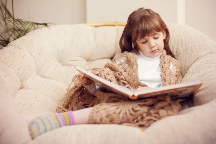 beauty child in shawl reading a ...