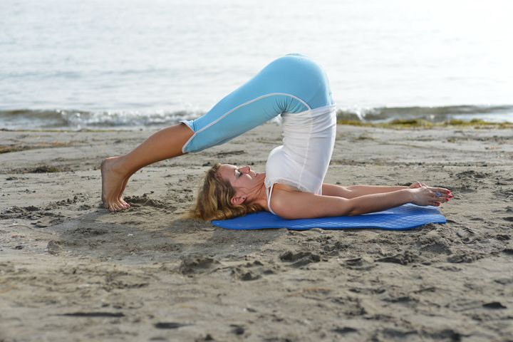 yoga by the ocean  young woman...
