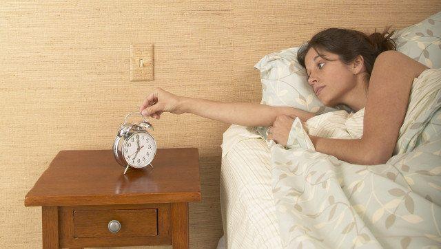 young woman setting alarm clock