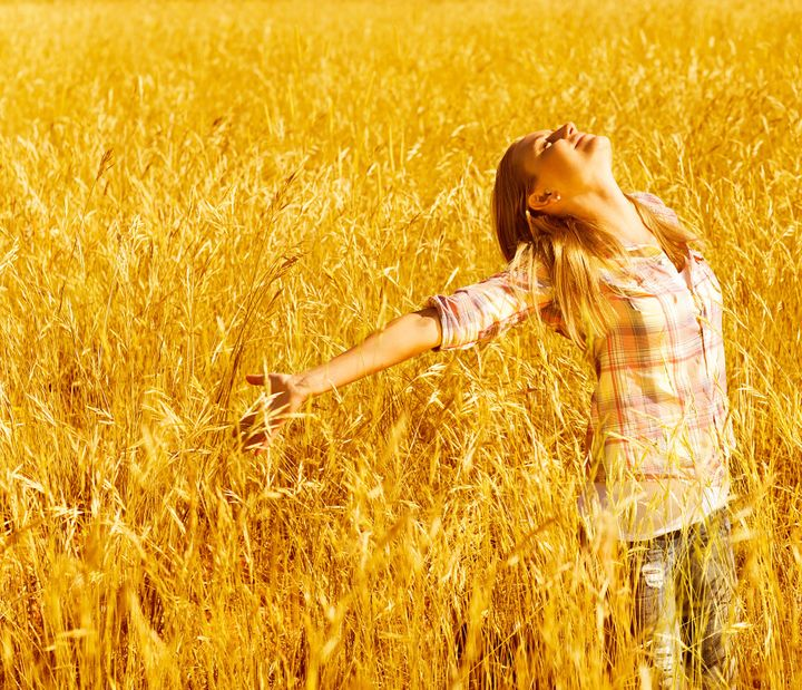 Picture of cheerful teenager having fun in countryside, cute happy female standing on wheat field with raised open hands and looking up, blond girl enjoying autumn nature, fall season