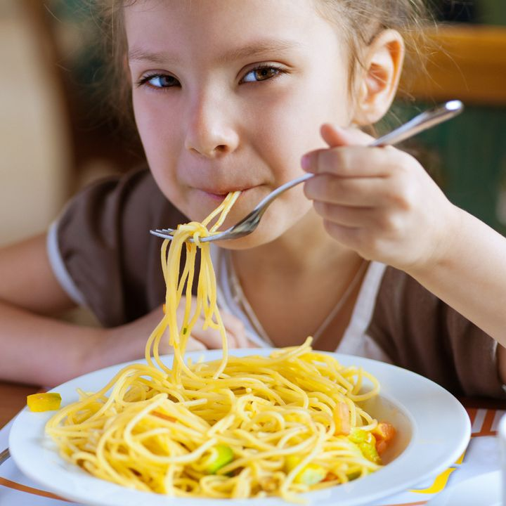 Small girl eating spaghetti with fork and smiles.