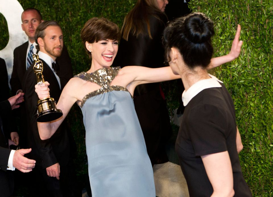 Anne Hathaway carrying her Oscar for best supporting actress greets comedian Sarah Silverman as they arrive for the 2013 Vani
