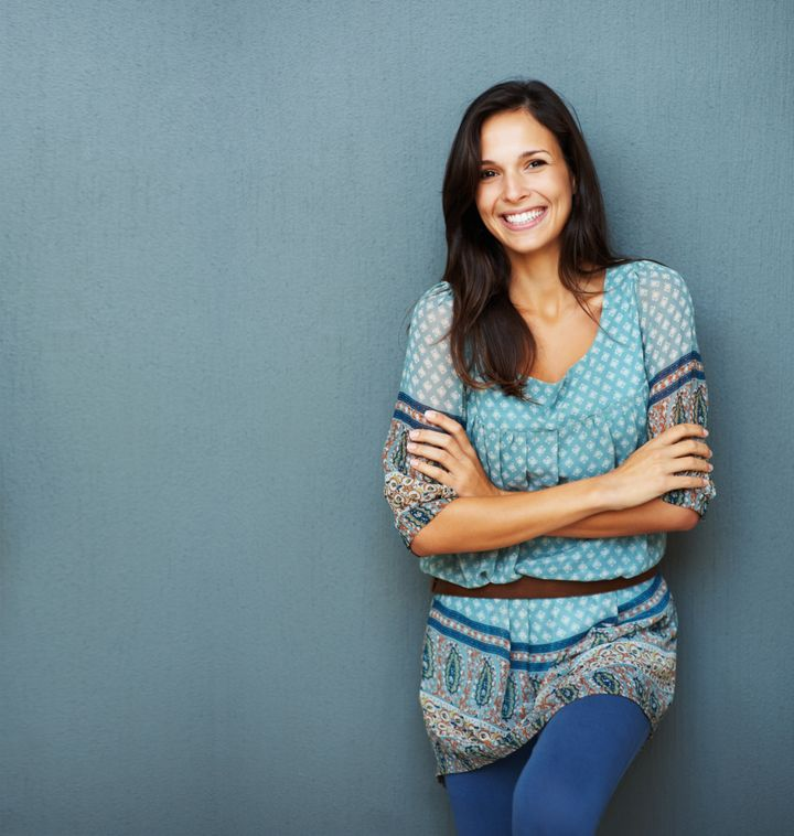 Confident woman with arms crossed against a blue background