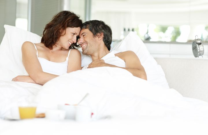 Relaxed middle aged couple lying on bed comfortably with breakfast in foreground