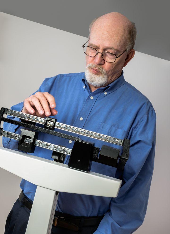 senior caucasian man weighing...