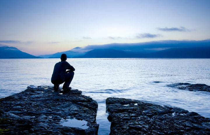 Man sitting on a small island watching the sunrise, slight cooling tone added.