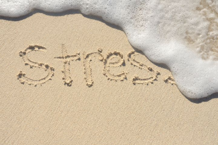 Relieving Stress, the Word Stress Being Washed Away by a Wave on a Beach