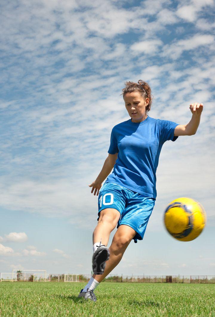 young girl kicking soccer ball...