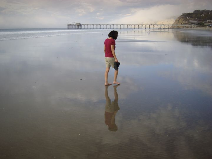Woman Walking on Mirror Beach. Great for themes of relationships, travel, contemplation, exploration, nature.