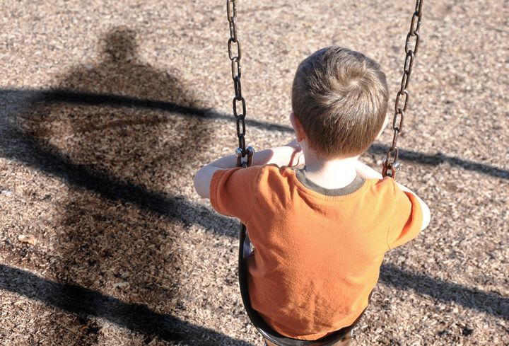 A young boy is sitting on a swing set and looking at a shadow figure of a man or bully at a playground. Use it for a kidnap,