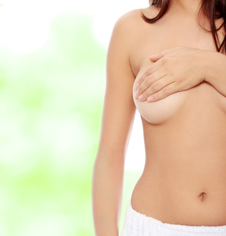 Topless woman body covering her breast with hand. Breast cancer concept