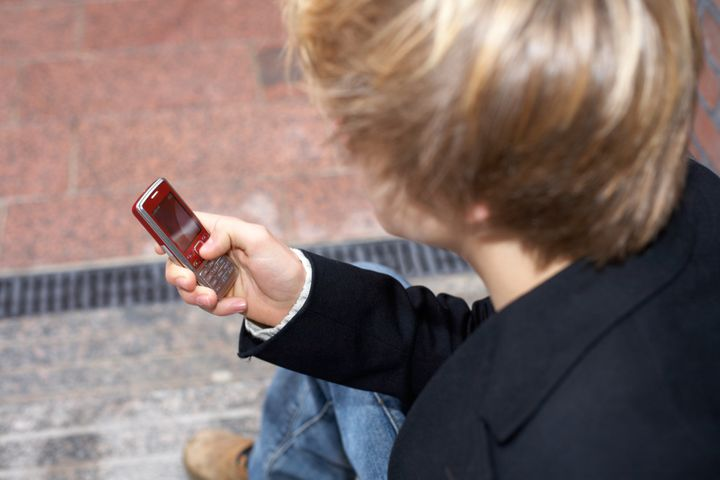 Teenage boy text messaging with mobile phone, high-angle view