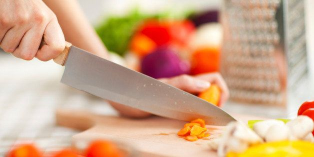close up of woman cutting vegetables on cutting board
