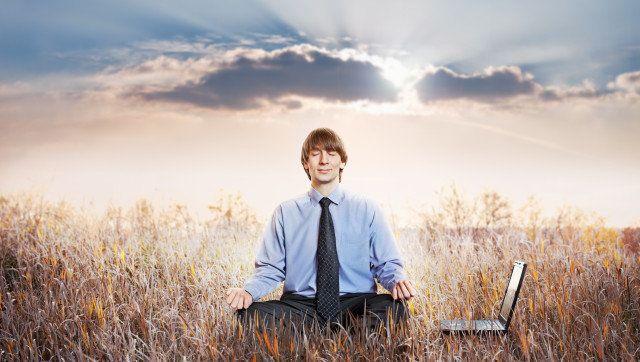 Businessman meditating in lotus pose. Business yoga