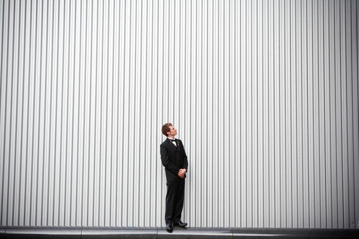 Uncertain groom standing near wall