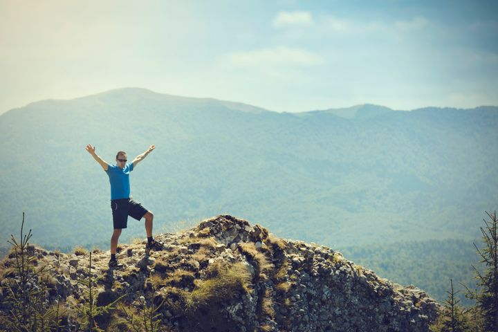 free man on mountain rock with arms raised.