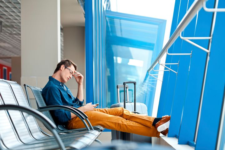 Young adult man waiting for his flight at the airport lounge and using a smart phone.
