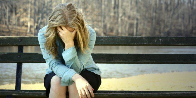very sad blonde girl holding her head on a bench