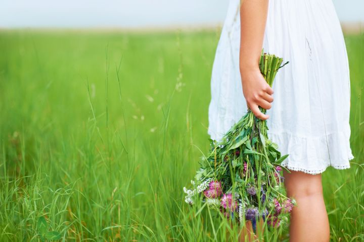 Cropped image of a woman holding flowers behind her back while walking in a field
