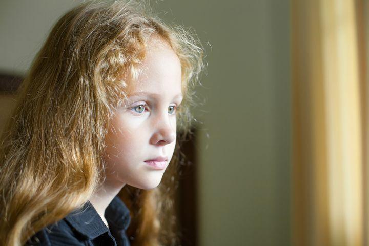 sad little girl sitting near...