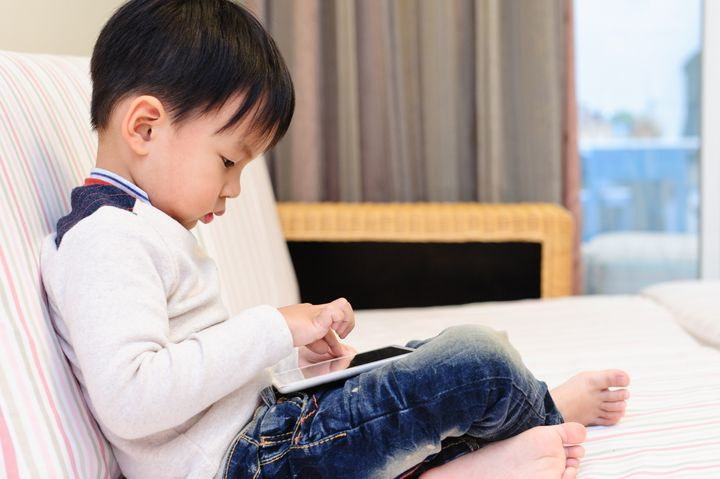 The little boy in the living room on the sofa using digital tablet to play games.