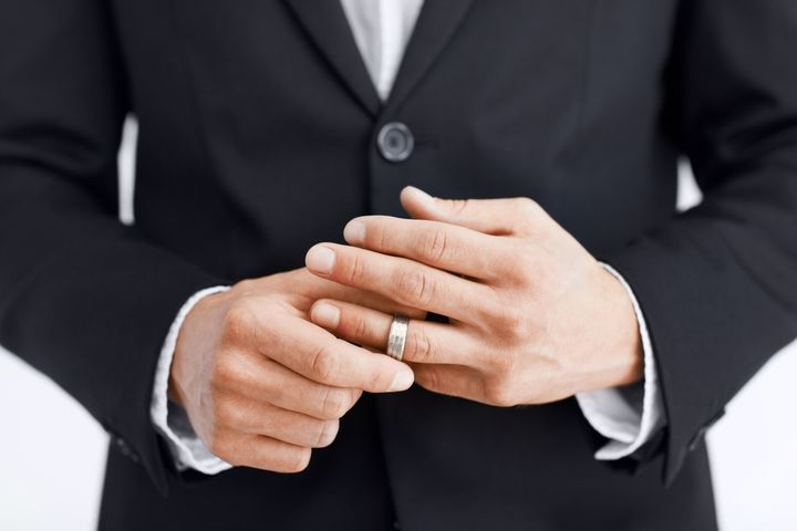 Cropped view of a married man's hands as he removes his wedding ring