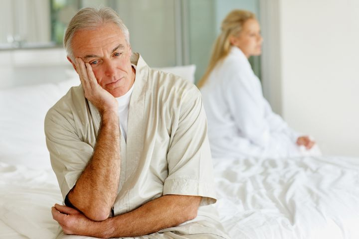 Senior man and his wife in a conflict sitting separately on the bed