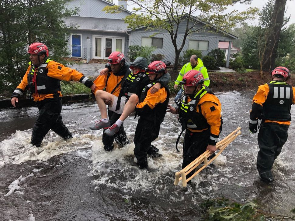 Rescue workers from New York rescue a man from flooding in River Bend, North Carolina.