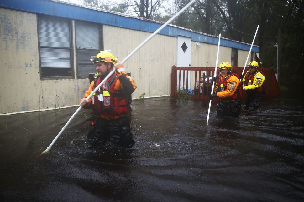 Boone County Fire Rescuers check for occupants in a home surrounded by floodwaters in Bolivia, North Carolina.