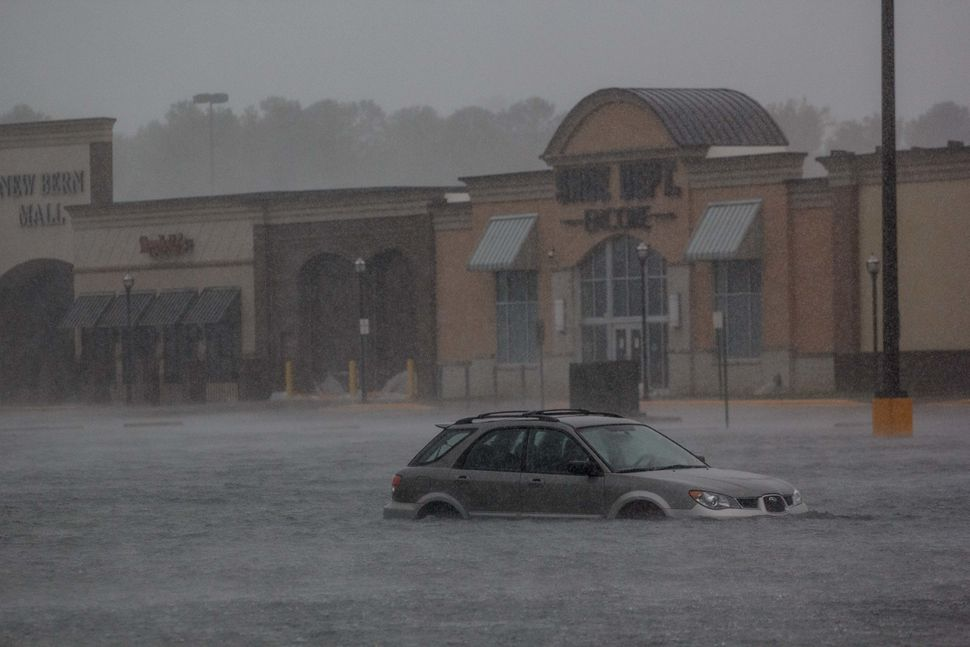 A car is seen in a flooded parking lot outside New Bern Mall in New Bern, North Carolina.