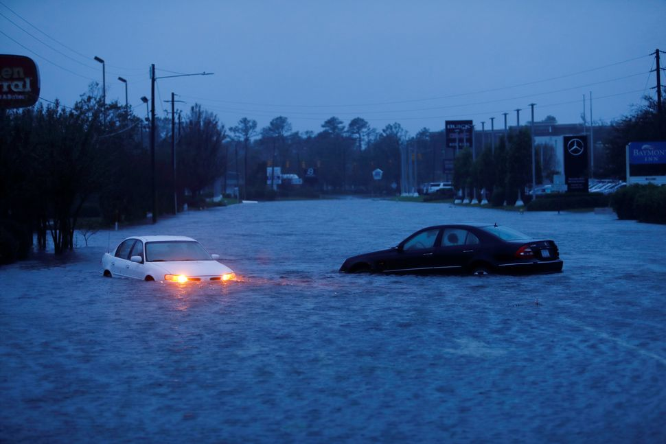 An abandoned car's hazard lights continue to flash as it sits submerged in rising floodwaters in Wilmington.