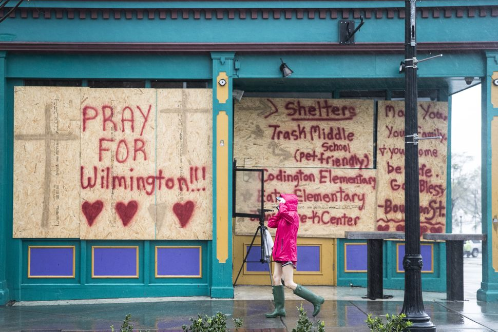 A pedestrian passes a boarded up property display in Wilmington, North Carolina.