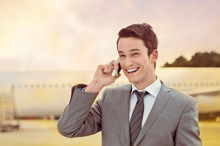 Outdoor portrait of excited young adult businessman standing in front of airplane and talking on a mobile phone.
