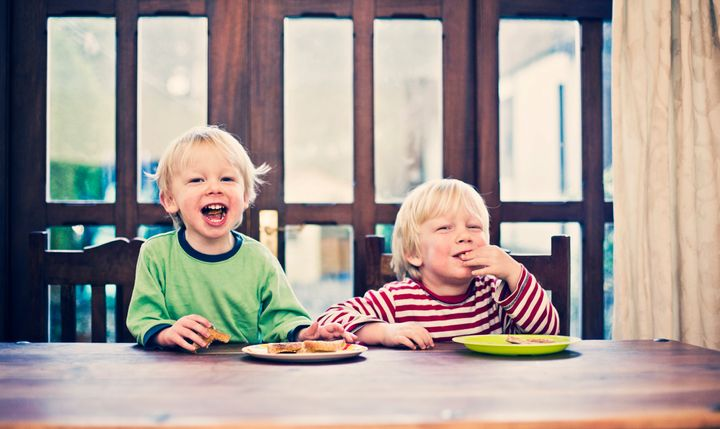 Two happy smiling little brothers sat at breakfast table eating toast.