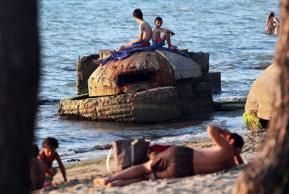 People sunbath atop of a decrepit communist era bunker on the shore in Qerret beach on July 13, 2011.   (GENT SHKULLAKU/AFP/G