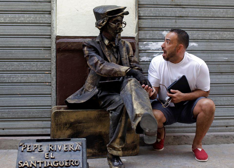 Retired baseball player Rey Ordonez, right, stops to joke with a street artist as he takes a stroll through Havana, Cuba, Sun