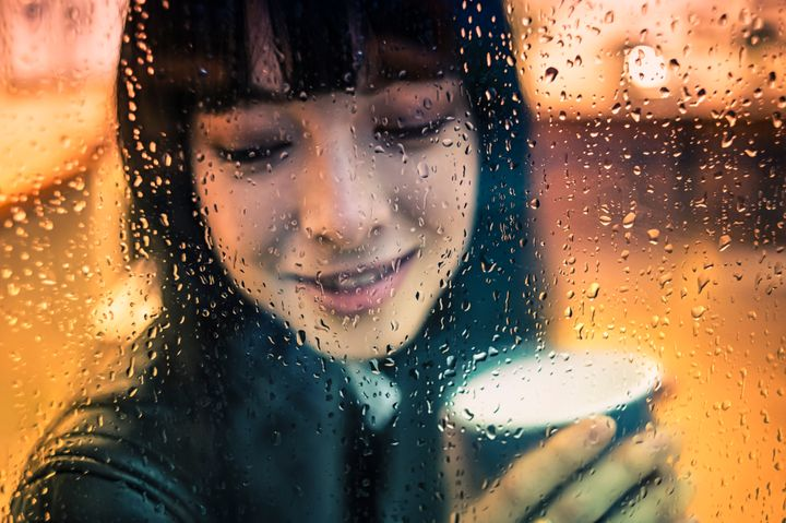 Young woman drinking hot coffee during a winter rainy day