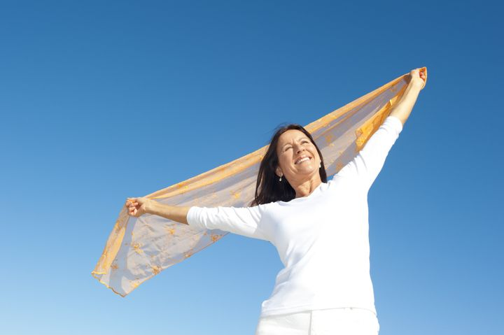 Happy, confident and attractive senior woman with positive attitude, isolated with blue sky as background and copy space.