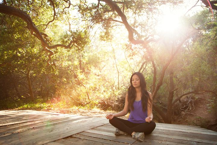 Young Woman Meditating In Woods
