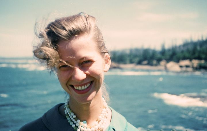 Woman poses in front of the ocean, her hair falling over one eye, wearing her trousseau of chic fitted blazer and fashionable faux pearl necklace.