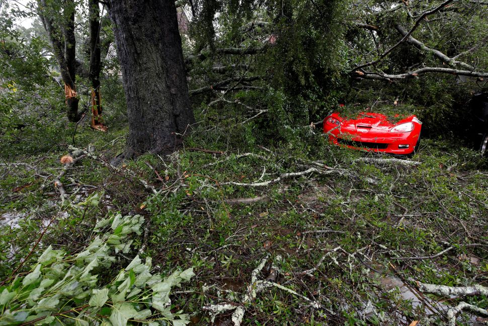 Leaves, branches and other debris surround and cover a sports car in Wilmington, North Carolina.