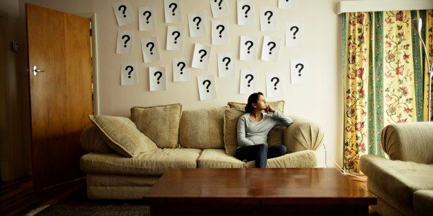 Woman sitting on sofa with question marks on wall.